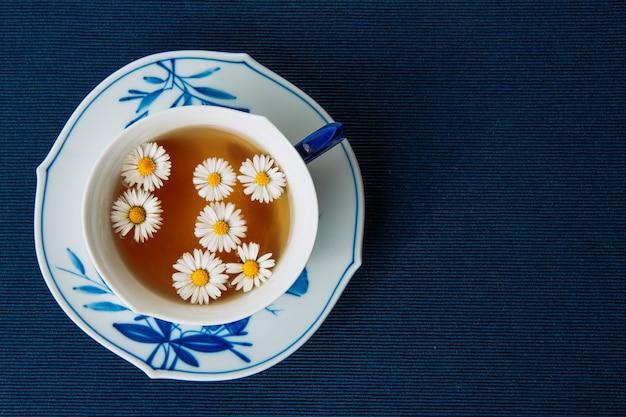 Aromatyczna herbata rumiankowa w filiżance i sosie na ciemnym podkładce. leżał płasko.