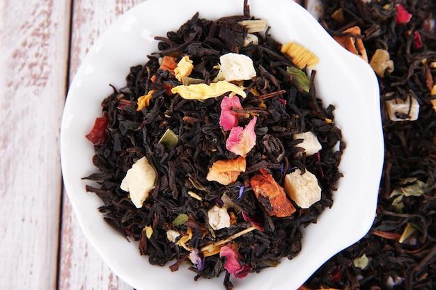 Aromatyczna herbata sucha w miseczkach na drewnianym