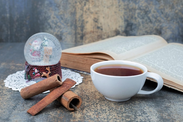 Aromatyczna herbata w białej filiżance z cynamonem na marmurowym stole