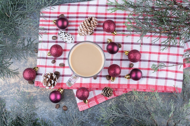 Aromatyczna kawa z szyszkami i bombkami na obrusie. zdjęcie wysokiej jakości
