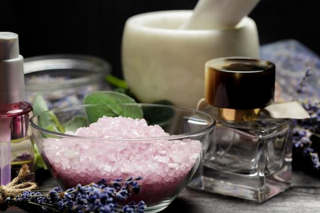 Aromatyczna kompozycja lawendy, ziół, kosmetyków i soli na ciemnym blacie