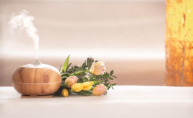 Aromatyczna lampa z dyfuzorem olejkowym na stole z pięknym wiosennym bukietem tulipanów.