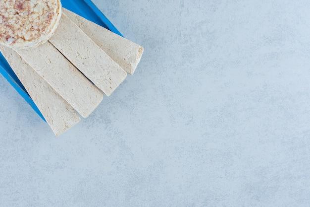 Aromatyczne ciastka ryżowe dmuchane na niebieskim talerzu z marmuru.
