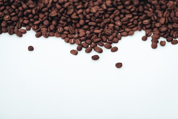 Aromatyczne ciemnobrązowe ziarna kawy na białym tle widok z góry z miejscem na kopię