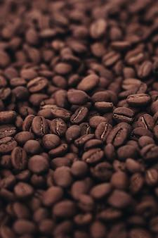 Aromatyczne ciemnobrązowe ziarna kawy w tle widok z góry pionowe zdjęcie z efektem ziarna filmu