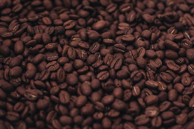 Aromatyczne ciemnobrązowe ziarna kawy w tle widok z góry zdjęcie z efektem ziarna filmu