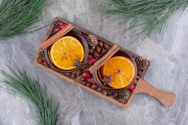 Aromatyczne filiżanki herbaty z cytryną i cynamonem na drewnianej desce.