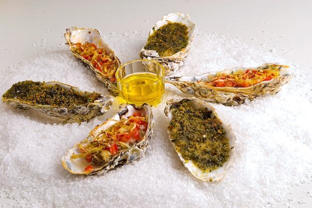 Aromatyczne ostrygi z porem, pomidorem, parmezanem i masłem oraz posiekaną cebulą.