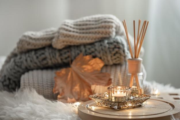Aromatyczne pałeczki bambusowe w butelce z pachnącym płynem ze świecami na drewnianej tacy na rozmytym tle.