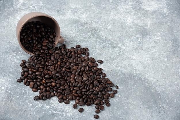Aromatyczne palone ziarna kawy z kubka na marmurowej powierzchni.