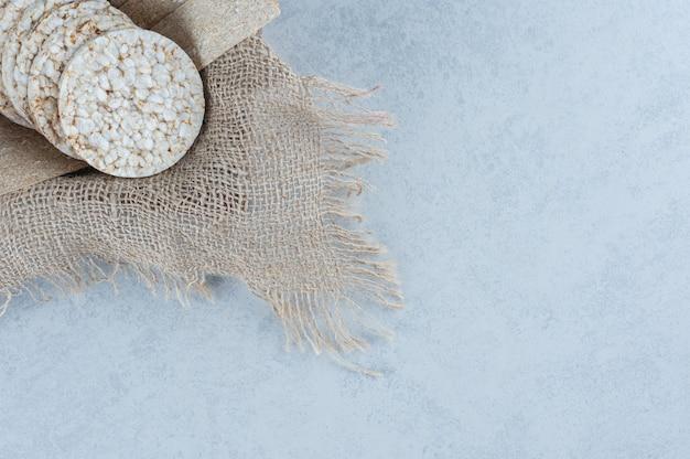 Aromatyczne pieczywo chrupkie na ręczniku w pudełku z marmuru.
