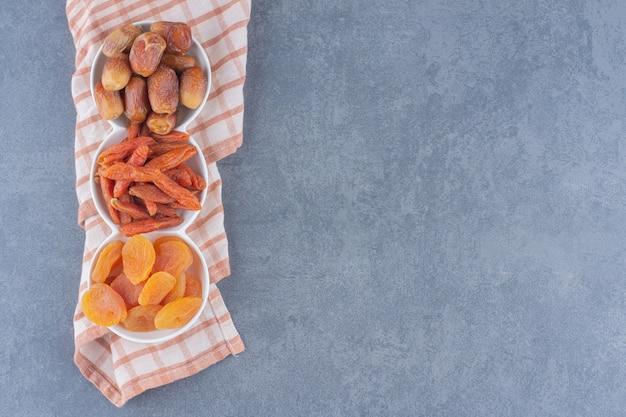 Aromatyczne suszone owoce w miseczkach na ręczniku, na marmurowym tle.