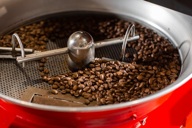 Aromatyczne ziarna kawy umieszczone w nowoczesnym sprzęcie z schładzaczem do ziarna. koncepcja przemysłu. nowoczesna maszyna służąca do prażenia fasoli. palarni kawy wlewanej do cylindra chłodzącego.