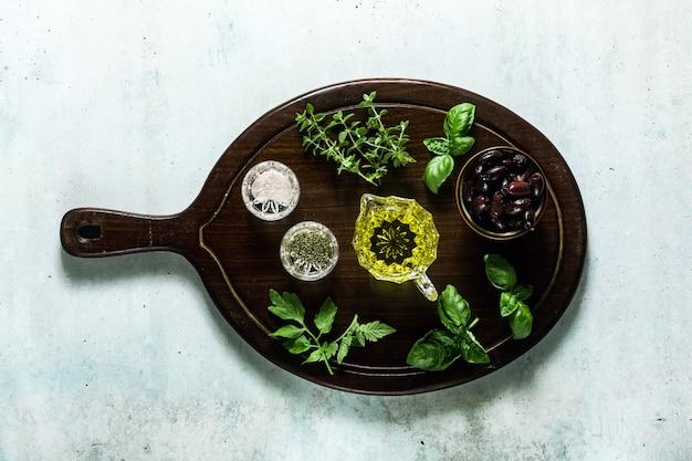Aromatyczne zioła do gotowania i oliwa z oliwek na drewnianej desce na stole. składniki