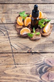 Aromatyczny olejek mandarynkowy w ciemnej bańce, olejek kosmetyczny z mandarynki na drewnianym stole, miejsce na kopię.