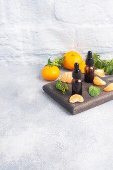 Aromatyczny olejek mandarynkowy w ciemnym bąbelku, olejek kosmetyczny z mandarynki na jasnoszarym tle