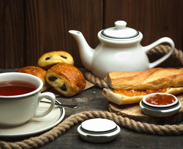Aromatyzowana herbata i bochenek chleba posmarowany dżemem