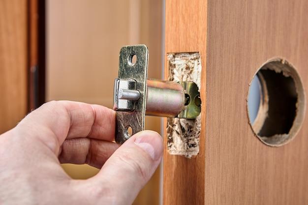 Arpenter wpycha zespół zatrzasku do otworu końcowego podczas instalowania zamykanej klamki drzwi.