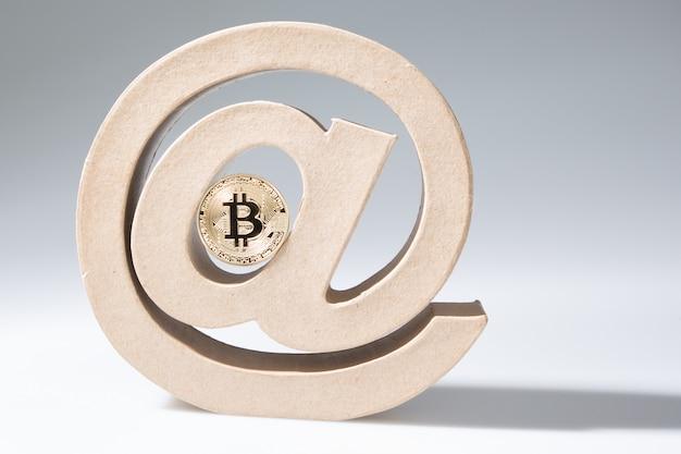 Arroba przy znaku z jednym złotym bitcoinowym pojęciem kryptowaluty