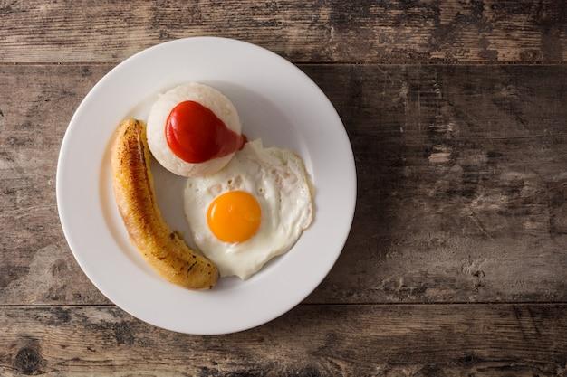 Arroz a la cubana typowy kubański ryż ze smażonym bananem i jajkiem na talerzu na drewnianym stole odgórnego widoku kopii przestrzeń