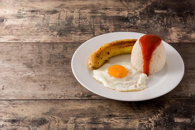 Arroz a la cubana typowy kubański ryż ze smażonym bananem i jajkiem sadzonym na talerzu na drewnianym stole