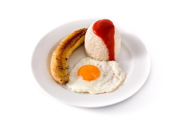 Arroz a la cubana. typowy kubański ryż ze smażonym bananem i jajkiem sadzonym na talerzu