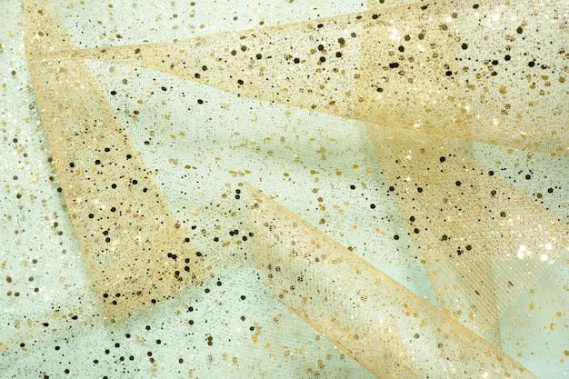 Art chic tło. kształty stożków wykonane z przezroczystej tkaniny ze złotym brokatem na jasnoniebieskim tle. streszczenie, wakacje.