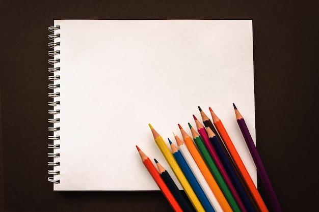 Art sketchpad kredki na brązowym tle, powrót do koncepcji szkoły. akcesoria szkolne, przestrzeń lub tekst na płasko