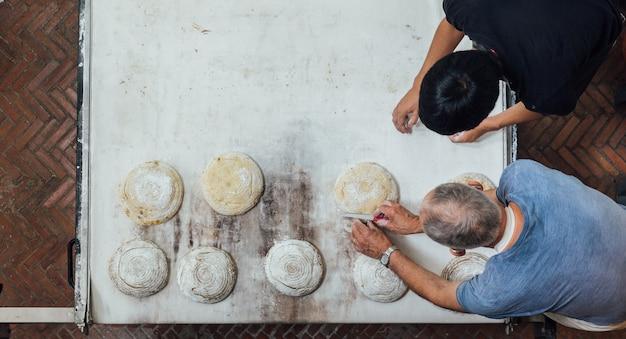 Artisan baker uczy swojego ucznia, aby pokroić ciasto chlebowe drożdżowe przed pieczeniem w piekarniku elektrycznym