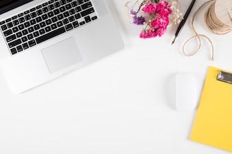 Artykuły papiernicze i bukiet w pobliżu laptopa