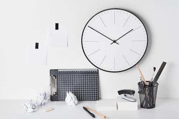 Artykuły biurowe i zegar ścienny na białym tle