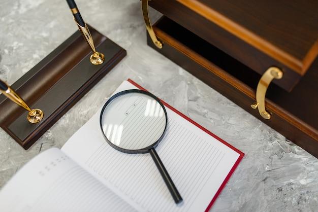 Artykuły biurowe, notatnik i lupa na stole w sklepie papierniczym, nikt. asortyment w sklepie, akcesoria do modelowania, sprzęt szkolny