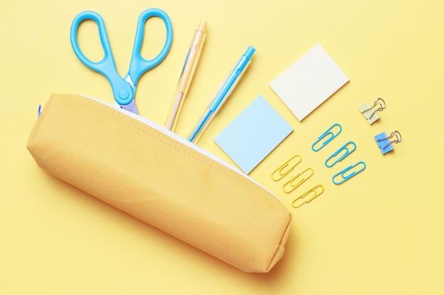 Artykuły biurowe, nożyczki i długopisy na żółtym, płaskim ułożeniu