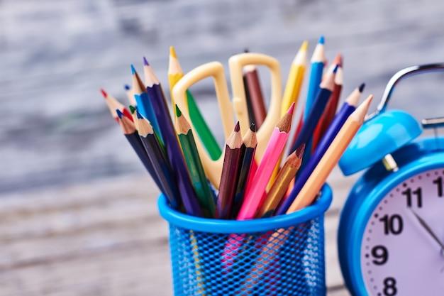 Artykuły papiernicze i budzik. kolorowe ołówki i nożyczki. czas na zajęcia plastyczne.