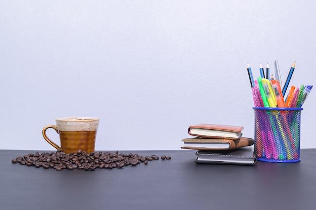 Artykuły papiernicze i kawa na biurku