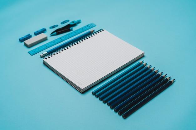 Artykuły papiernicze - książka, ołówek, linijka na niebieskim tle.