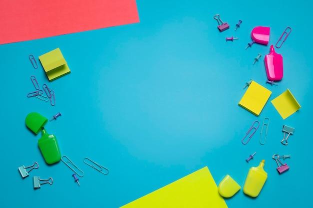 Artykuły papiernicze na niebieskim tle z wolnym miejscem na tekst artykuły szkolne lub biurowe