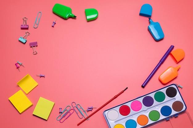 Artykuły papiernicze na różowym tle z wolnym miejscem na tekst artykuły szkolne lub biurowe