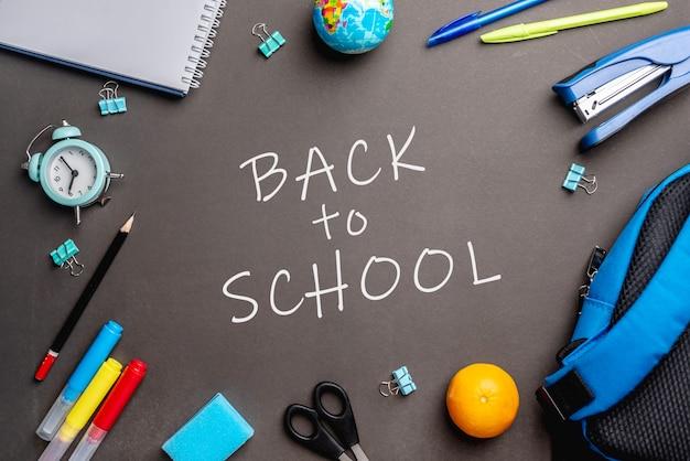 Artykuły papiernicze szkolne wokół słów powrót do szkoły na czarnym tle