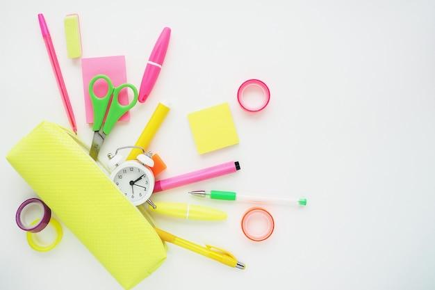 Artykuły papiernicze w jasnych kolorach spadające z jasnożółtego piórnika. płaski układ, widok z góry na białym tle.