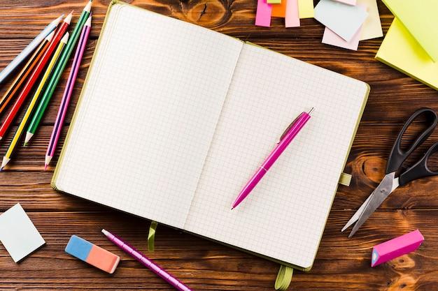 Artykuły papiernicze wokół otwartego notatnika