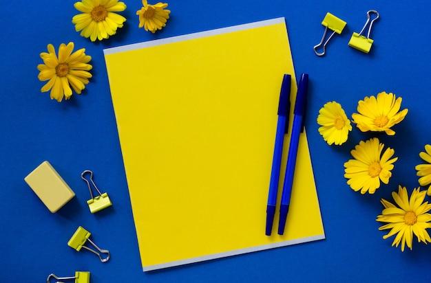 Artykuły papiernicze z kwiatami nagietka na niebieskim tle