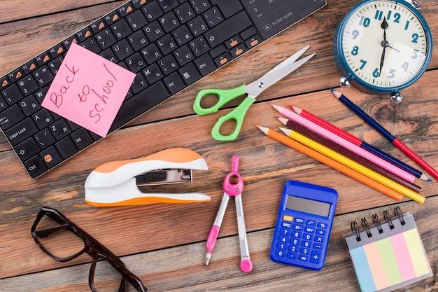 Artykuły piśmienne szkolne akcesoria na drewnianym biurku. powrót do koncepcji szkoły. zszywacz z nożyczkami i klawiaturą na stole.