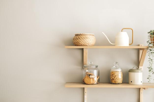 Artykuły spożywcze i kuchenne na drewnianych półkach w nowoczesnej jasnej kuchni