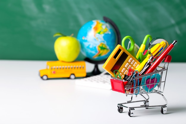 Artykuły szkolne, autobus szkolny i wózek na zakupy z różnymi rzeczami