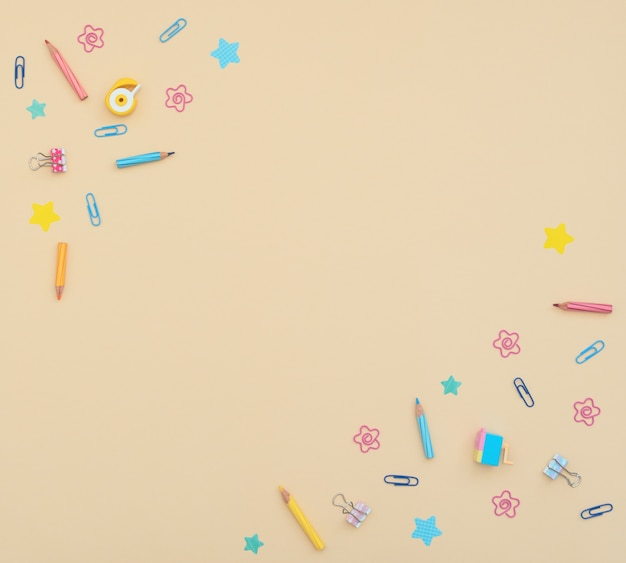 Artykuły szkolne i biurowe ołówki, spinacze, papier firmowy, naklejki, gumki na żółtym tle.