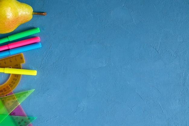 Artykuły szkolne i gruszka na niebieskim tle