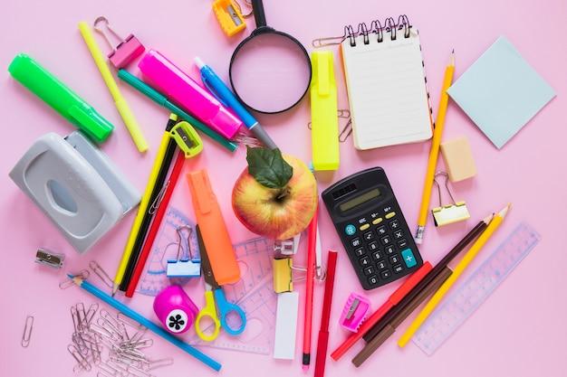 Artykuły szkolne i jabłko układane w losowy sposób