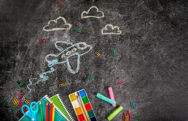 Artykuły szkolne i samoloty malowane kredą na tablicy