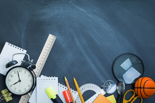 Artykuły szkolne na tle tablicy nauczycielskiej